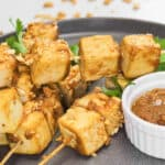 baked tofu on skewers with a small bowl of delicious peanut sauce