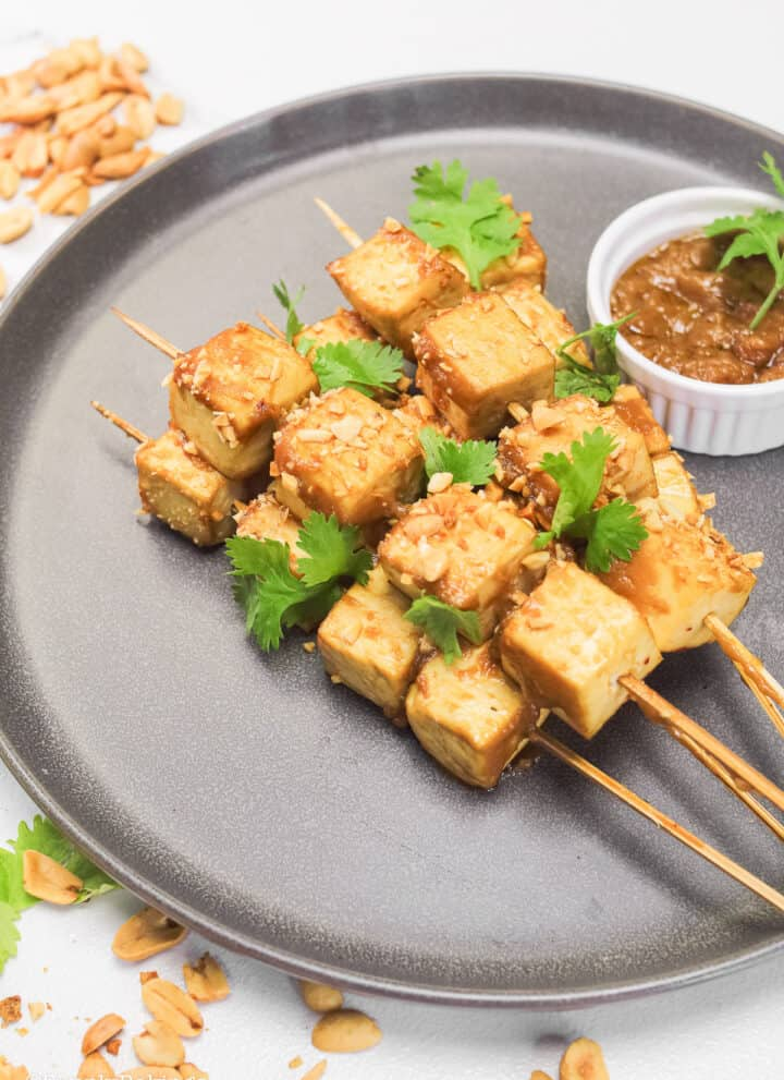 tofu skewers on a peanut sauce of a gray plate