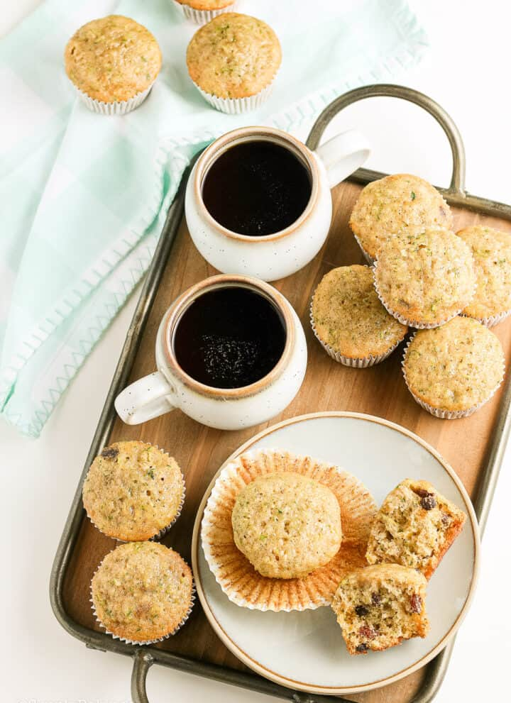 zuchinni muffins and cups of chocolate drinks in a tray
