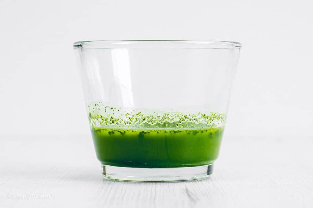 matcha powder and lukewarm water mixture in a small bowl