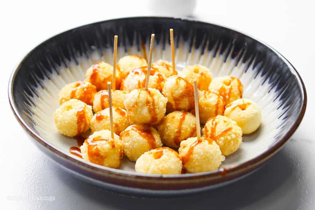 karioka balls on a black and white bowl with poked with toothpicks