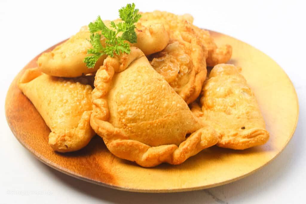 empanadas on a round wooden plate