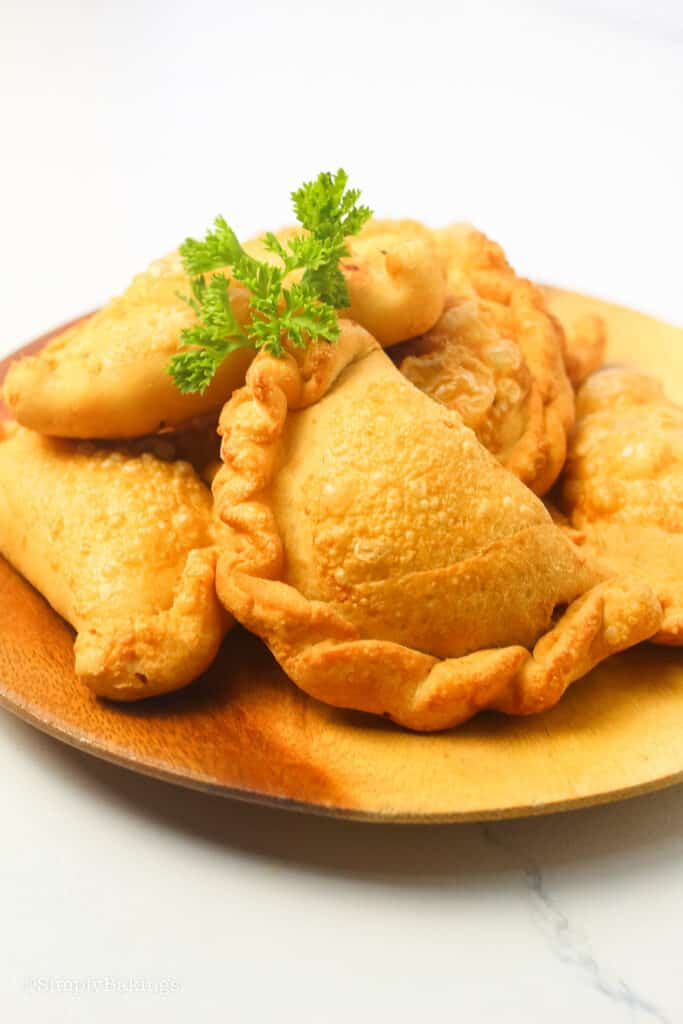 cooked empanadas on a round wooden plate and garnished with cilantro