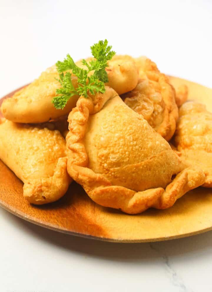 delicious empanadas on a round wooden plate