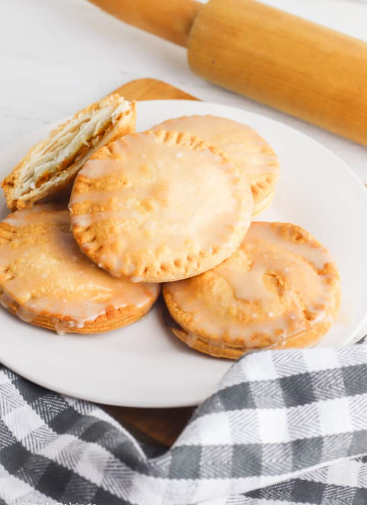 air-fried mini pumpkin pies on a white plate beside a rolling pin beside