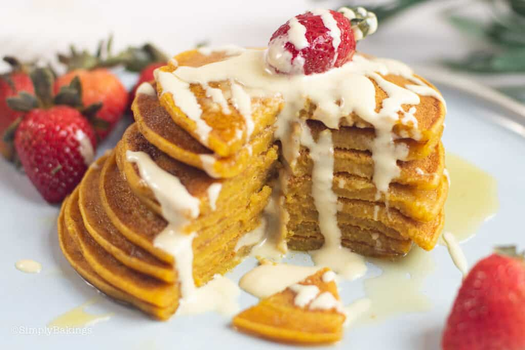 kalabasa (squash) pancakes topped with fresh strawberry and drizzled with sweetened milk