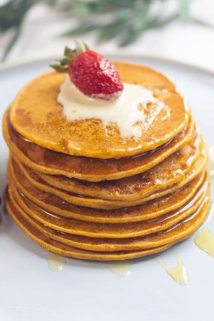 stack of squash pancakes drizzled with syrup and topped with fresh strawberry