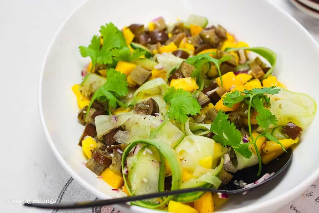 savory mango salad on a white bowl with a spoon