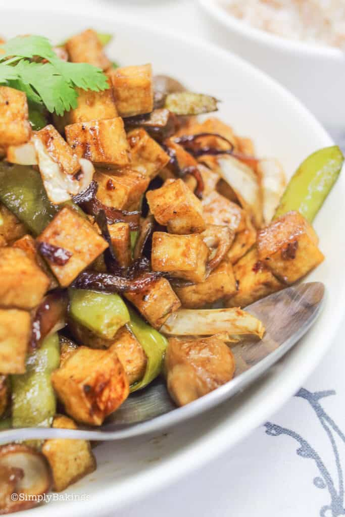 delicious stir fry tofu in a white bowl with a stainless spoon