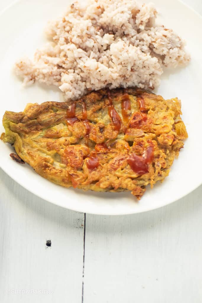 a serving of tortang talong with steamed rice on a white plate