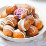 ube donut holes in a white bowl