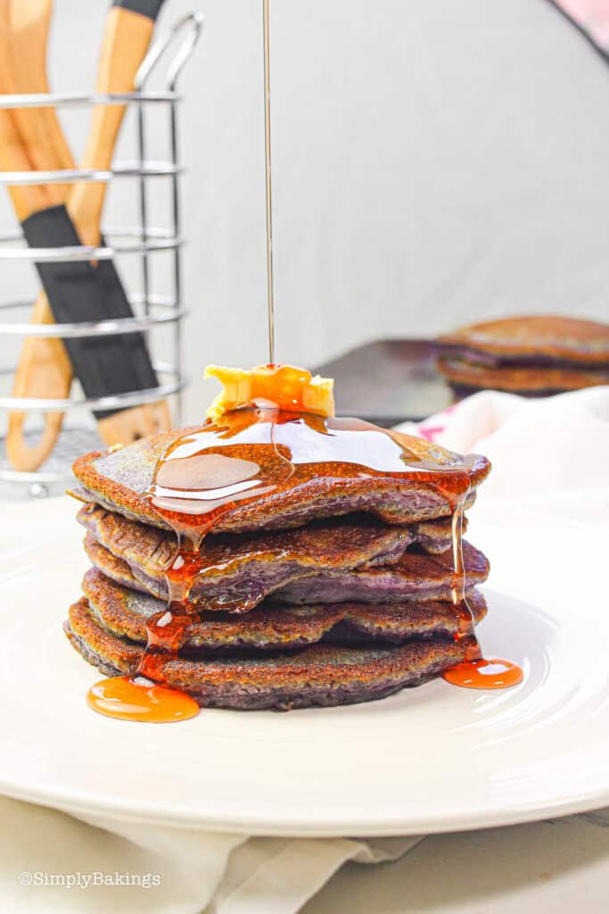 delicious ube pancakes topped with butter and maple syrup on a white plate